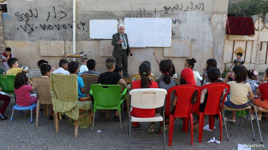أستاذ متقاعد يقدم روسا مجانية لطلابه في أحد شوارع كركوك