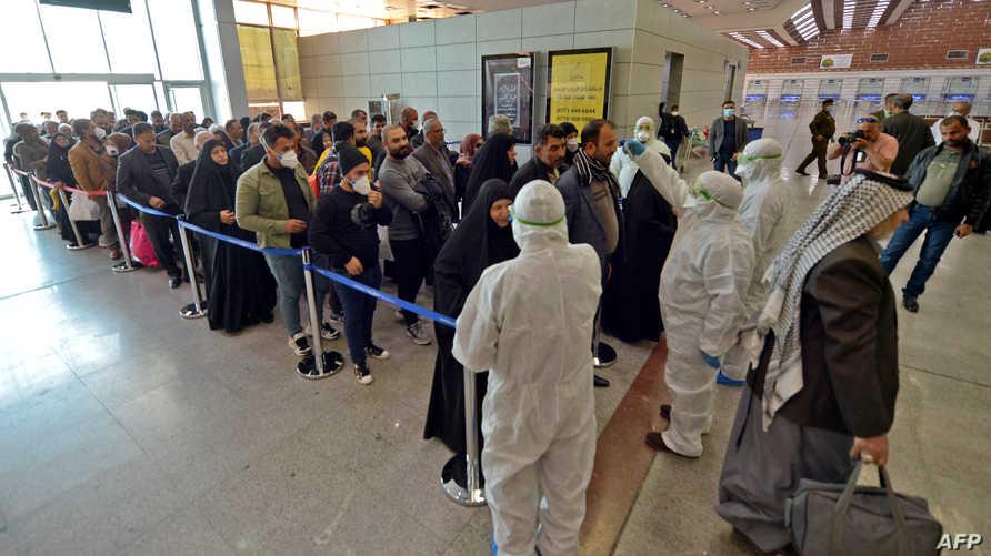 فريق طبي عراقي يفحص مسافرين قادمين من إيران بعد مقتل 8 إيرانيين بسبب فيروس كورونا المستجد- 21 فبراير 2020