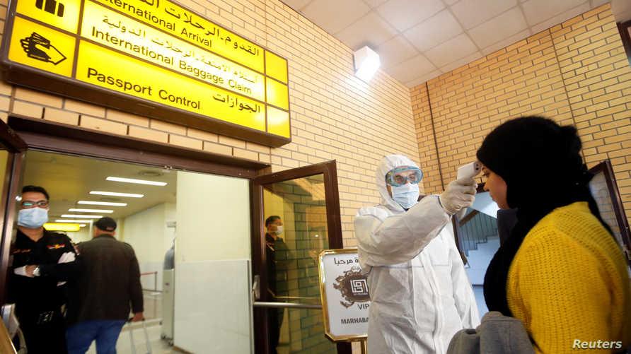 موظف بوزارة الصحة العراقية يفحص درجة حرارة الركاب لدى وصولهم إلى مطار البصرة