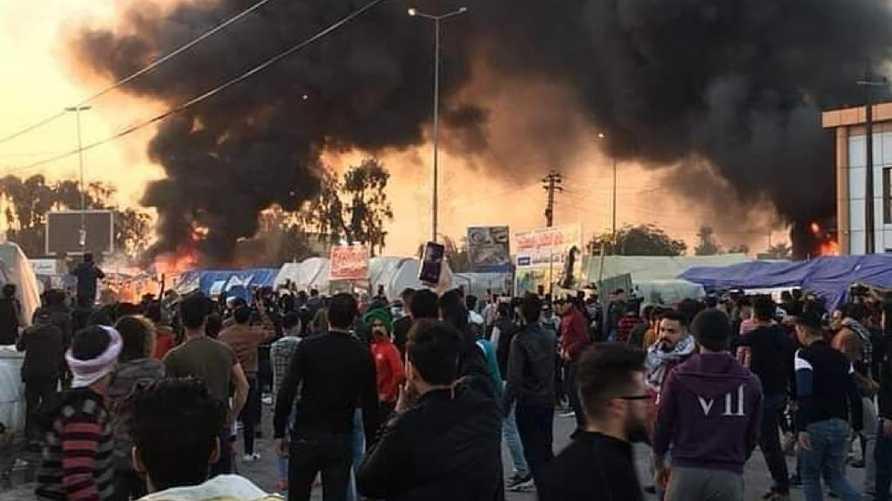 متظاهرون من النجف يقفون أمام دخان خيمهم المحترقة.. المصدر مواقع التواصل الاجتماعي
