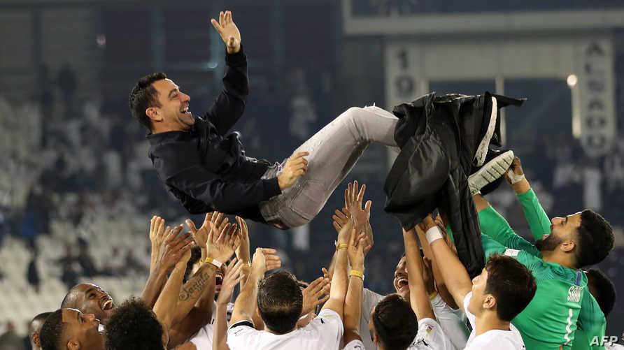 لاعبو السد القطري يرفعون مدربهم لاعب برشلونة الإسباني تشافي هرنانديز
