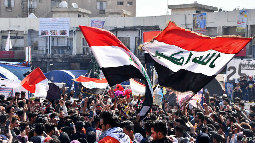 Student protesters, some wearing protective face masks, march with Iraqi national flags during an anti-government demonstration…