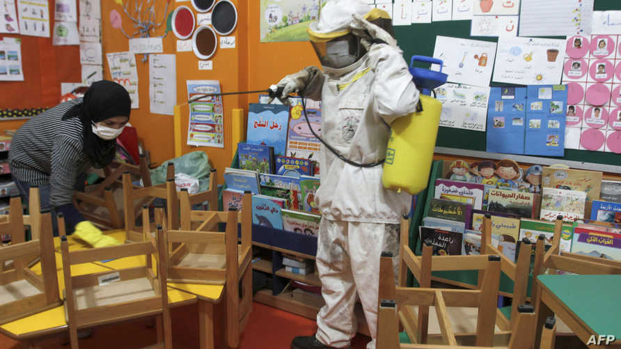 Lebanese workers spray disinfectant in classrooms and halls of a school in the coastal town of Rmeileh, 35 Kms south of the…