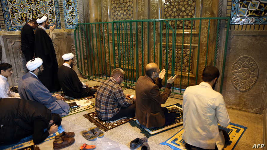 Iranians pray behind the closed doors of the Fatima Masumeh shrine in Iran's holy city of Qom on March 16 2020. - Iran closed…