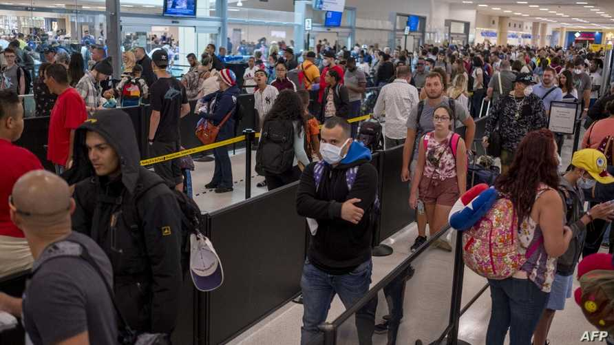 Travelers wait in line at a security checkpoint at the Luis Munoz Marin International Airport in San Juan, Puerto Rico on March…