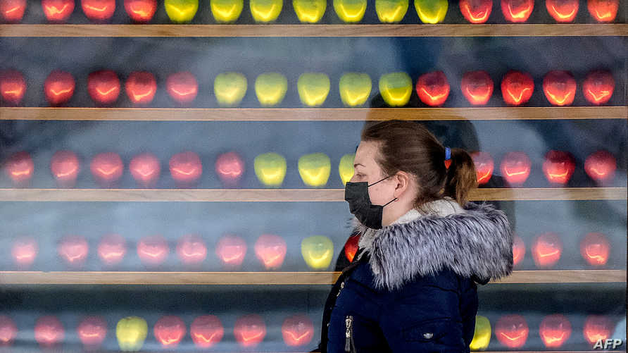A woman wearing a face mask, amid concerns of the COVID-19 coronavirus, walks past the shop window of a grocery store in…