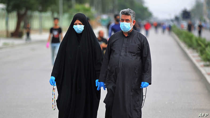 Iraqi shiite pilgrims wearing face-masks make their way to the shrine of Imam Moussa al-Kadhim in Baghdad's northern district…