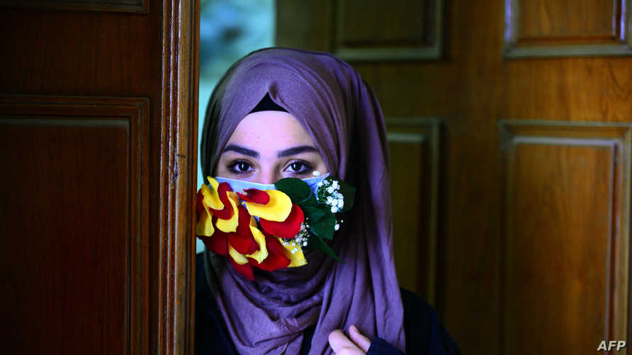 A woman is seen wearing a mask embellished with petals in the central Iraqi holy city of Najaf on March 21, 2020 amid the COVID…