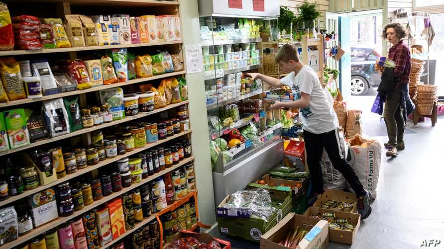 A member of staff at the community owned grocery shop, The Village Green, picks an emailed order from a local resident self…