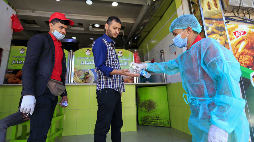 A worker wearing protective clothing sprays hand sanitiser on a customer's hand before he enters a restaurant in the Yemeni…