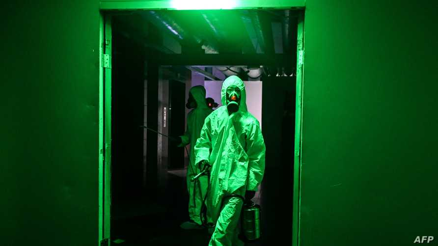 Workers wearing protective clothing disinfect a hotel as a preventive measure against the COVID-19 coronavirus in Yangon on…