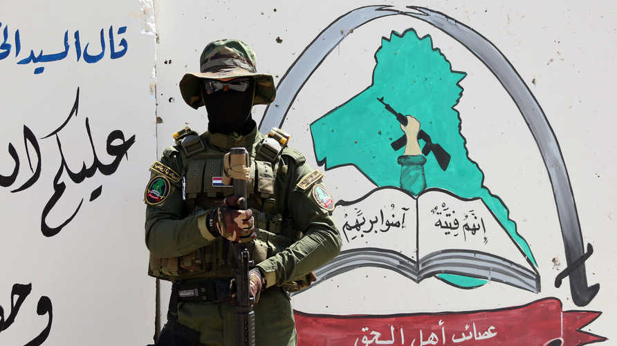 An Iraqi fighter of the Shiite group Asaib Ahl al-Haq (The League of the Righteous) stands guard outside the militia's…