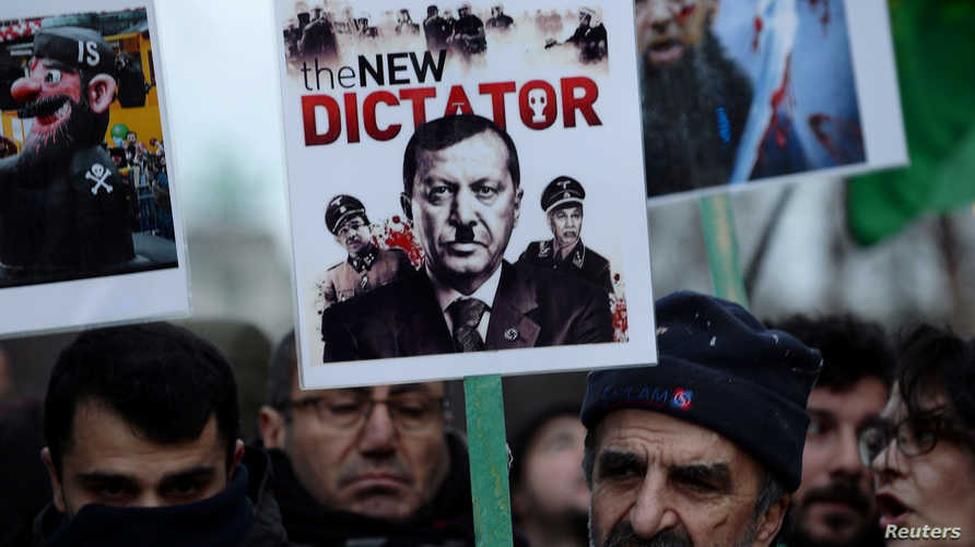A protester holds a banner depicting Turkish President Tayyip Erdogan during a demonstration against a visit of the president,…