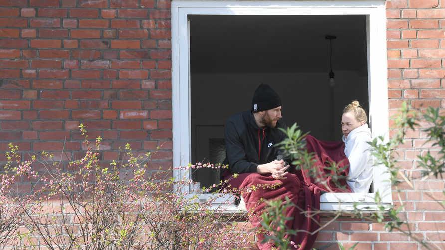 رجل وامرأة يجلسان على نافذة في هامبورع ويهدد وباء كورونا والإجراءات المتبعة للحد من انتشاره بزيادة الضغوط على العلاقات الزوجية