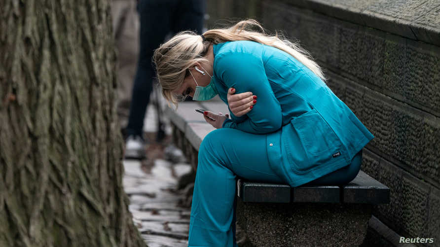 A healthcare worker sits on a bench near Central park in the Manhattan borough of New York City, U.S., March 30, 2020. REUTERS…