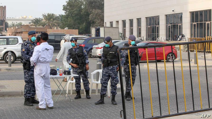 أفراد من الحرس الوطني الكويتي خارج فندق في العاصمة، حيث يخضع الكويتيون العائدون من إيران للحجر الصحي
