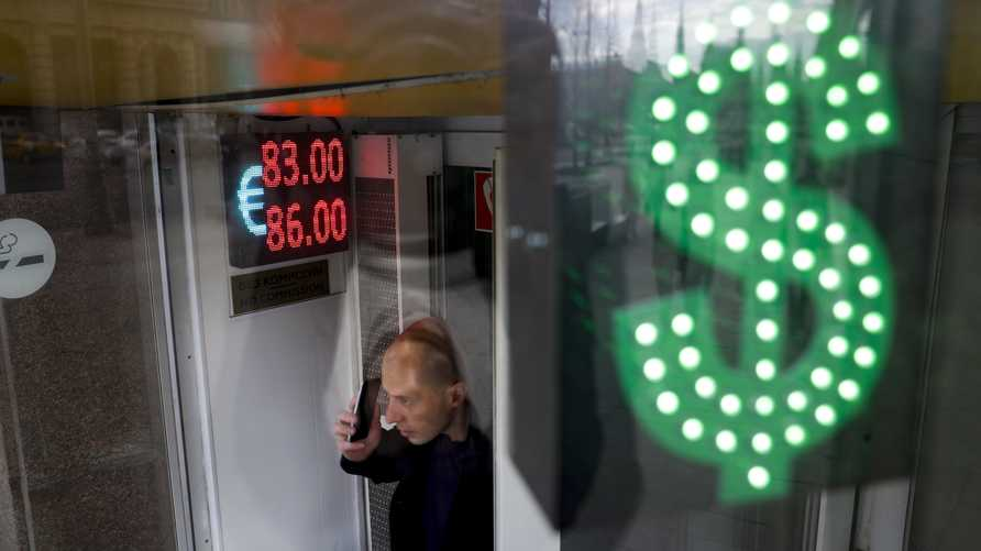 A man speaks on the phone at an exchange office screen showing the currency exchange rates of U.S. Dollar and Euro to Russian…
