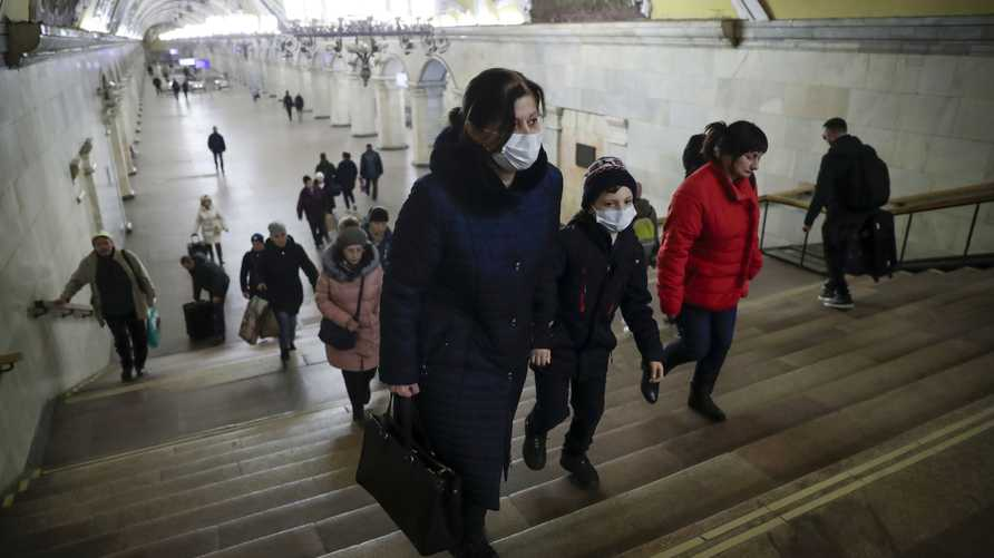 A woman and her child wear medical masks walk inside the Komsomolskaya Metro (subway) station in Moscow, Russia, Wednesday,…
