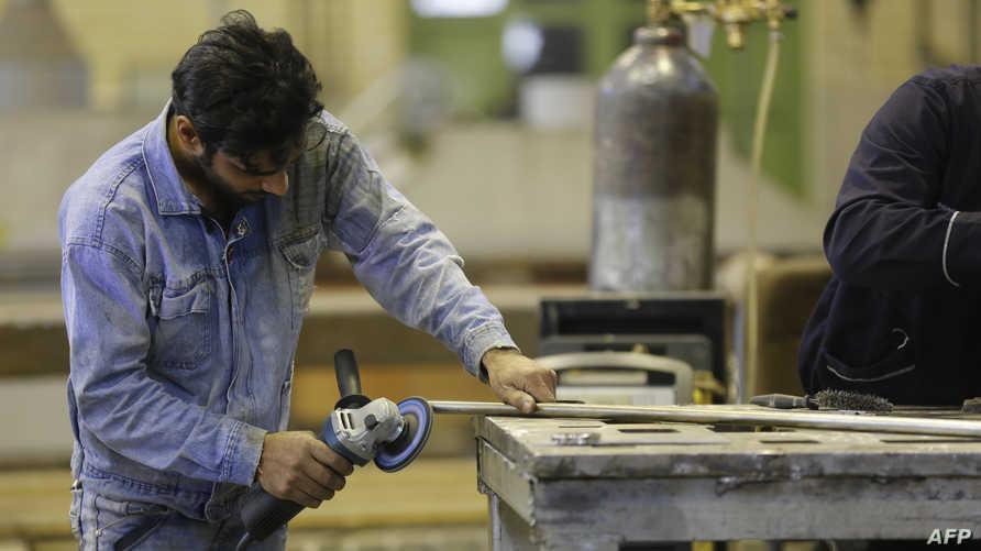 عامل إيراني في مصنع في حي شهريار وسط طهران