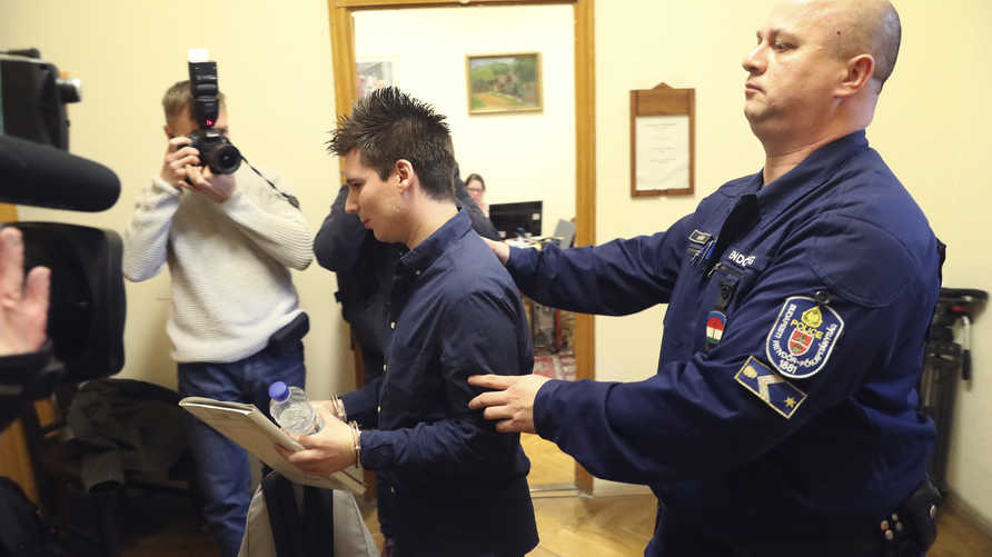 Football Leaks whistleblower Rui Pinto (C) is escorted by a judicial officer as he arrives at the Metropolitan Court in…