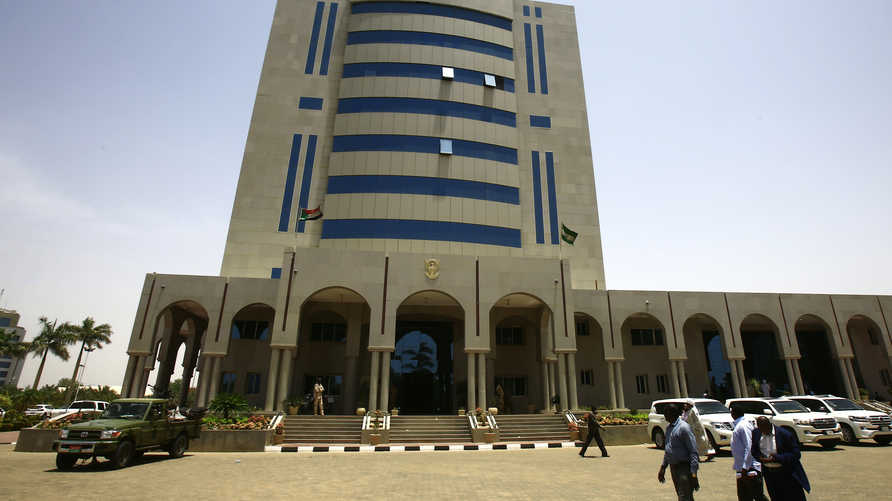 Pedestrians walk in front of the building housing the defence ministry in the capital Khartoum on April 12, 2019. - Sudanese…