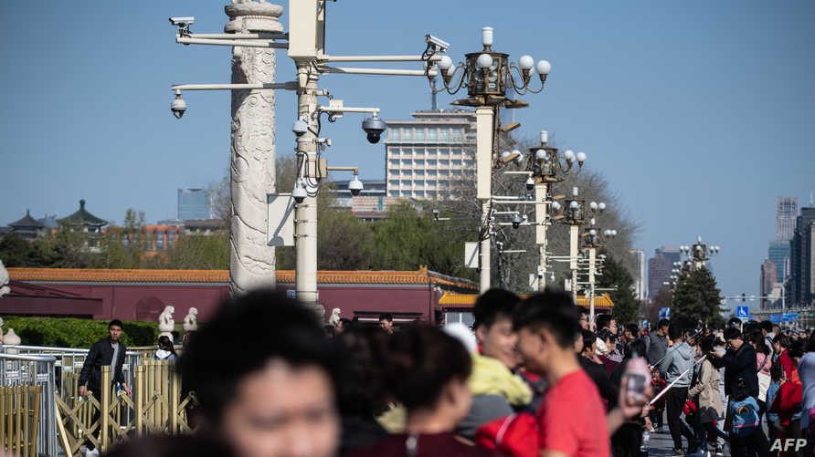 In this picture taken on April 2, 2019, surveillance cameras are seen above tourists as they visit Tiananmen Square in Beijing…