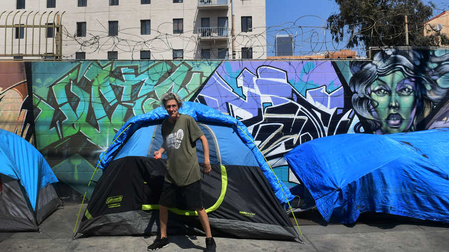 A homeless person stands in front on tents lining a sidewalk in in Los Angeles, California, on May 30, 2019 where figures…