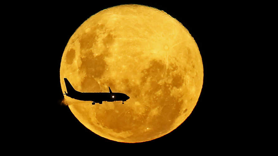 A plane passes in front of the full moon as seen from Curitiba, Brazil on March 9, 2020. - The supermoon is visible as the full…