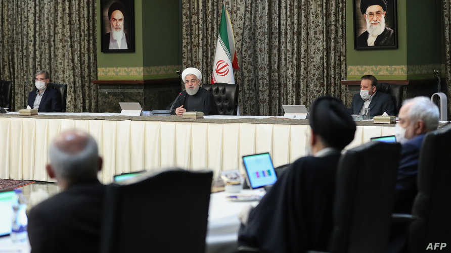 A handout picture provided by the Iranian presidency on March 11, 2020 shows President Hassan Rouhani (C), surrounded by…