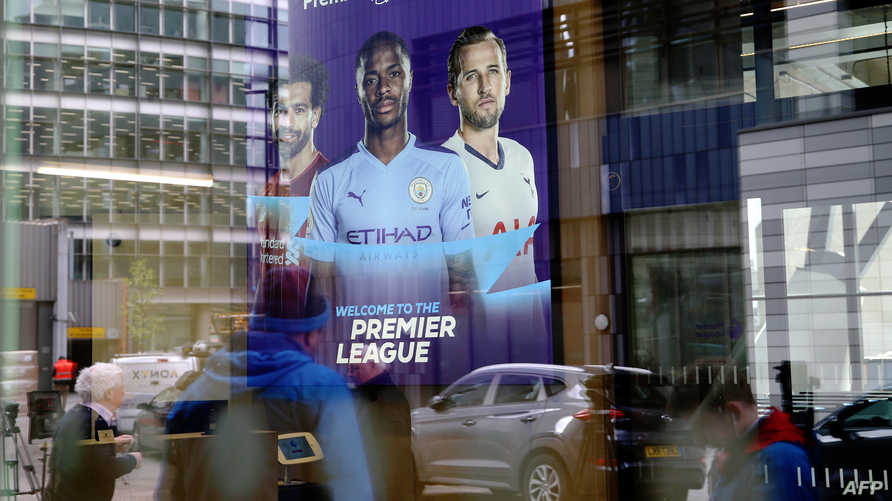 Members of the media are reflected in the glass at the headquarters of the English Premier League in London on March 13, 2020. …