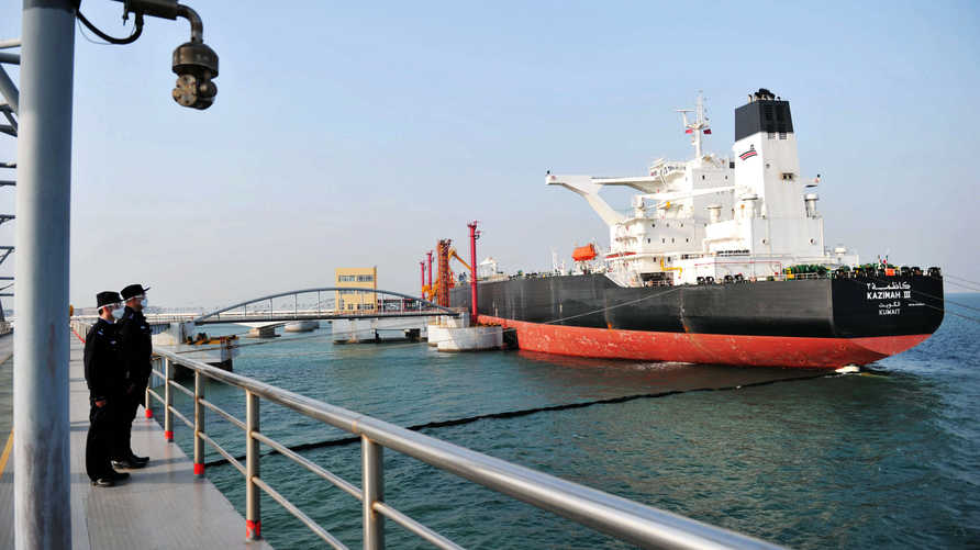 This photo taken on March 20, 2020 shows police officers keeping watch as a Kuwaiti oil tanker unloads crude oil at the port in…