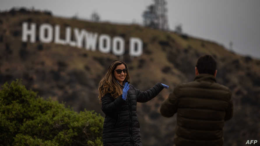 A woman wearing gloves poses below the Hollywood Sign in Hollywood on March 22, 2020, during the coronavirus (COVID-19)…