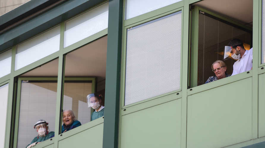 Medical personnel and hosts cheer from the windows of the Honegger nursing home where 35 people have died so far from…