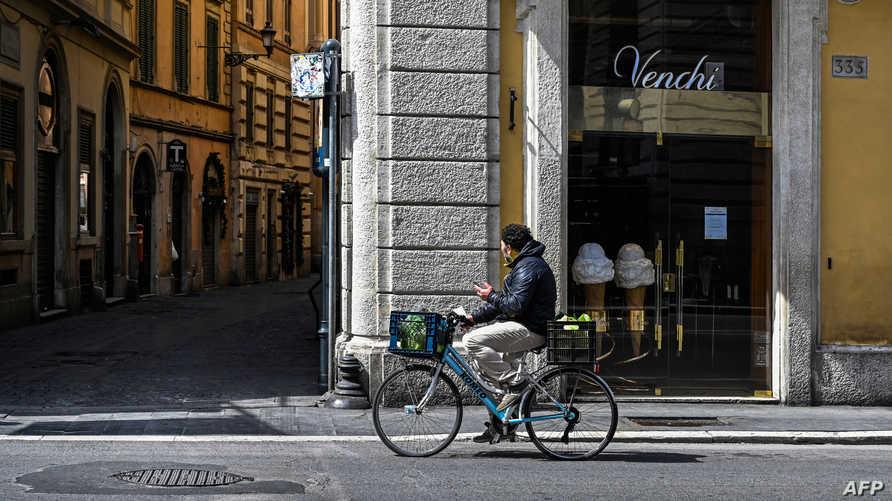 شخص يقود عجلة في روما وسط قيود على الحركة في عموم إيطاليا- ٣١ مارس ٢٠٢٠