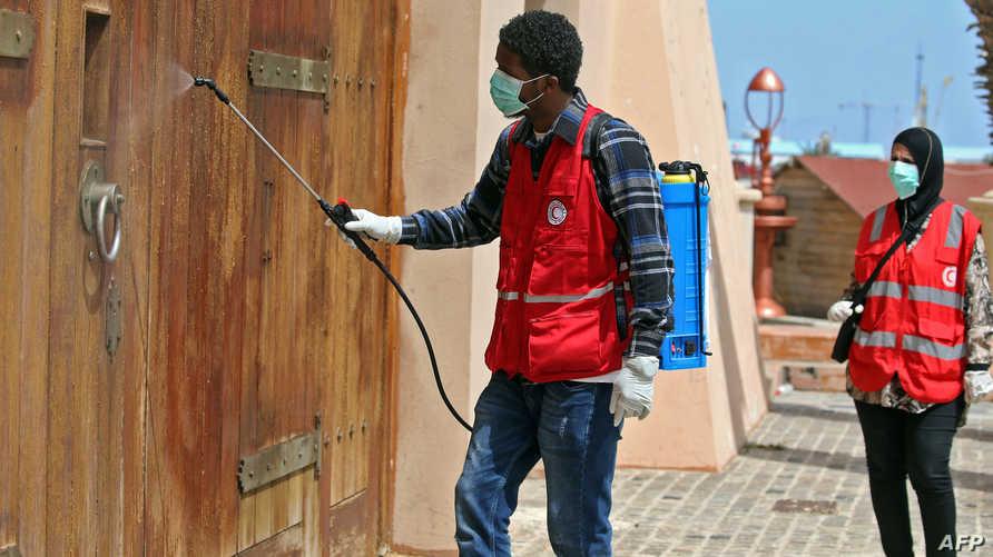 عناصر من الهلال الأحمر الليبي يعقمون جدران شوارع العاصمة الليبية من فيروس كورونا -١ أبريل ٢٠٢٠