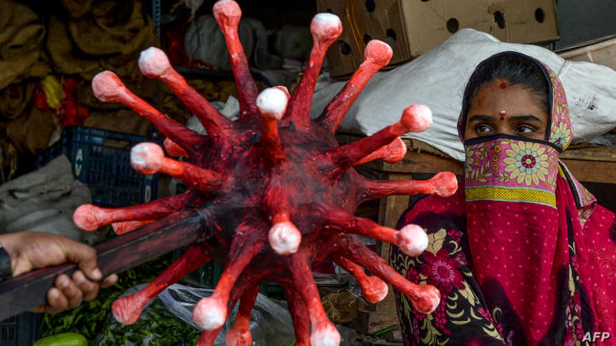 A policeman wearing a coronavirus-themed outfit composed of helmet, mace and shield, gestures towards a vendor (R) at a market…