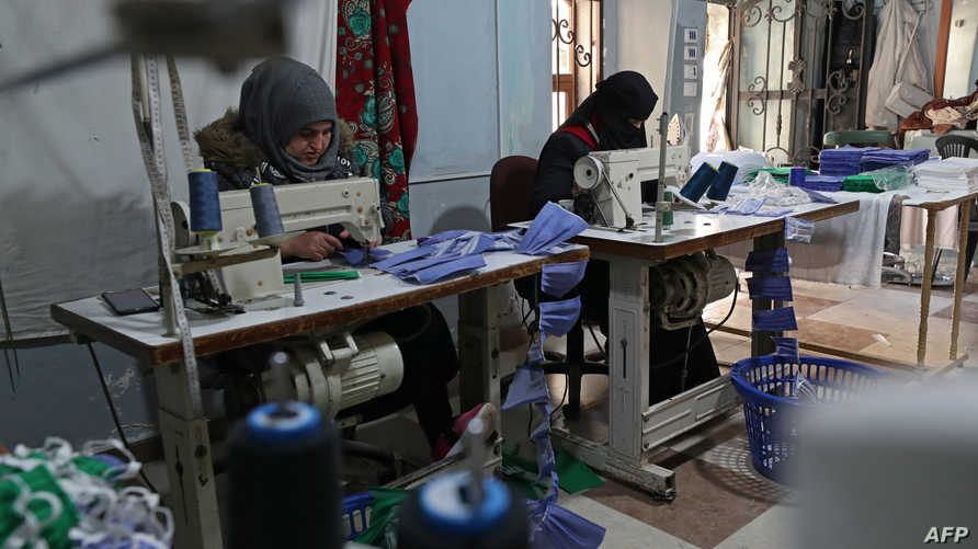 Syrian women sew protective masks against the coronavirus COVID-19 at a workshop belonging to humanitarian organisation…