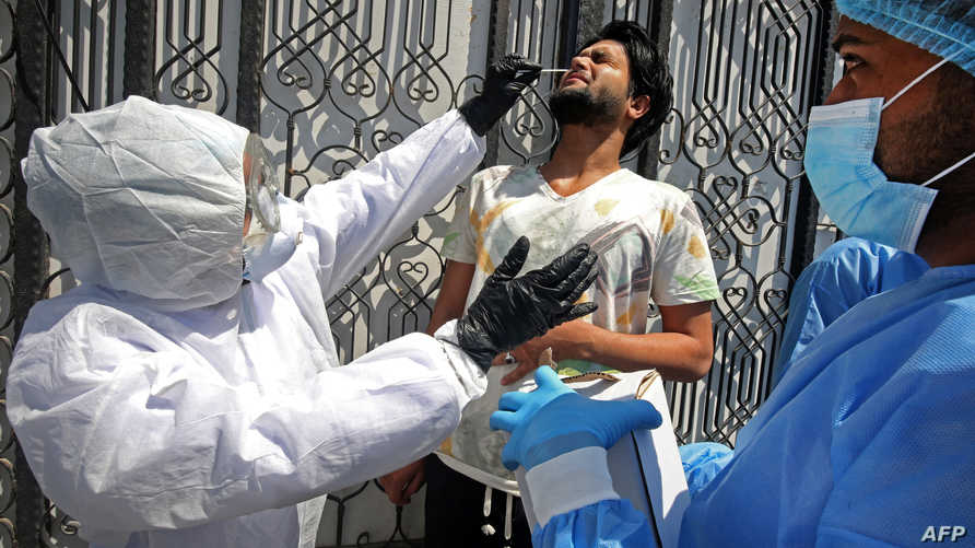 أطباء في مستشفى حكومي في العاصمة العراقية بغداد يأخذون عينة لفحص فيروس كورونا- 2 أبريل 2020