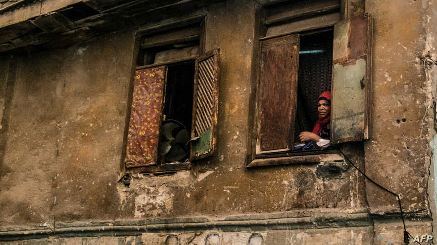 An Egyptian woman looks out a window near al-Azhar mosque in  Cairo on April 2, 2020, as most of the residents of the capital…