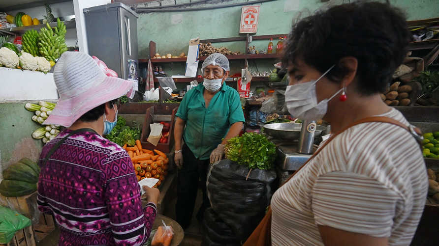 Shoppers wear face masks to prevent the spread of the new coronavirus at a neighborhood market in Lima, on April 2, 2020. -…