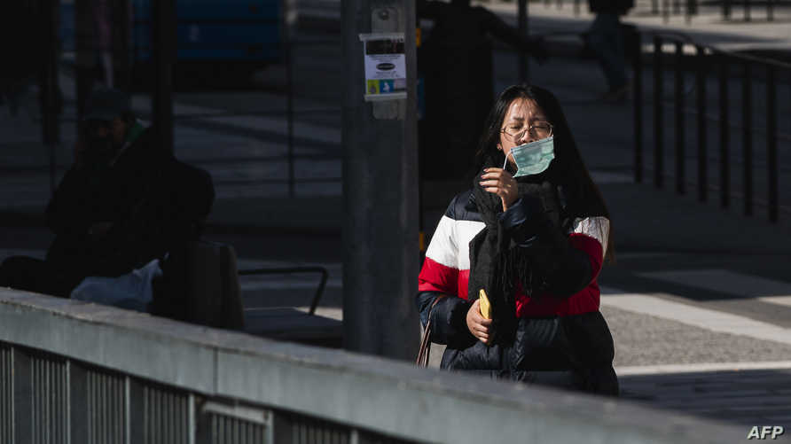 A woman takes off her protective face mask on April 6, 2020 in Stockholm, during the novel coronavirus Covid-19 pandemic. …