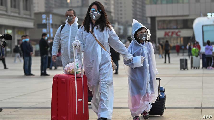 مواطنون من وهان يلبسون البزات الواقية ويغادرون المنطقة