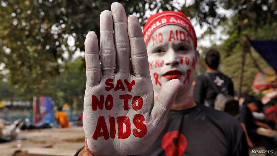 A man poses as he displays his hand and face painted with messages during an HIV/AIDS awareness campaign on the eve of World…