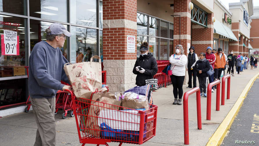 FILE PHOTO: A shopper passes near a self-distancing queue outside Trader Joe's, as they limited the amount of shoppers allowed…