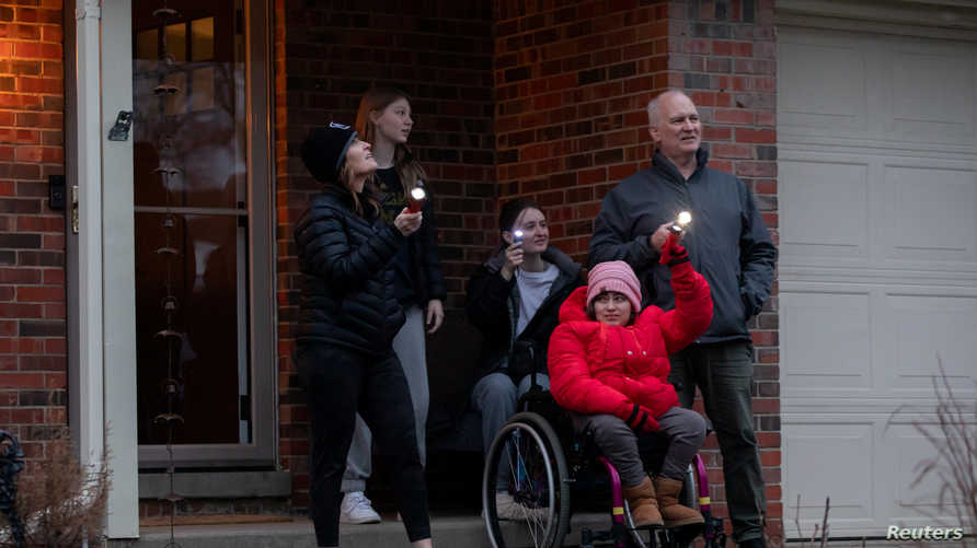 The Sovran family stands outside their front door shining flashlights towards their nearest hospital during the first night of …