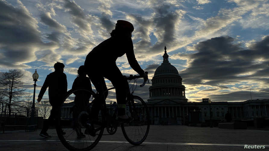 Walkers and cyclists take to the east front of the U.S. Capitol during the outbreak of the coronavirus disease (COVID-19), as…