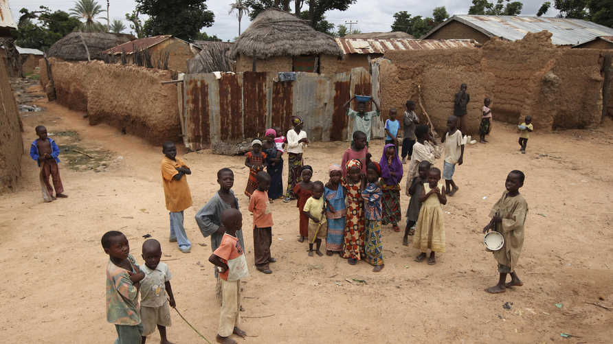 In this Monday, Sept. 6, 2010 photo, children gather in a village square as health workers spray family compounds with a…