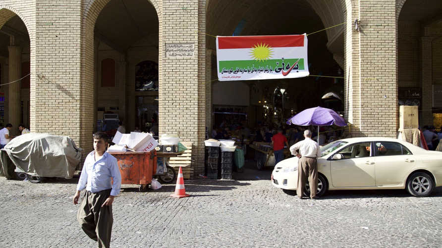 In this Thursday, Aug. 24, 2017 photo, a man walks past a campaign poster printed on a Kurdish flag urging people to vote yes…