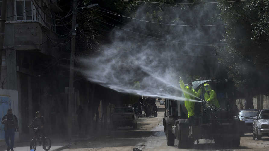 Workers wearing protective gear spray disinfectant as a precaution against the coronavirus, at the main road of closed market…