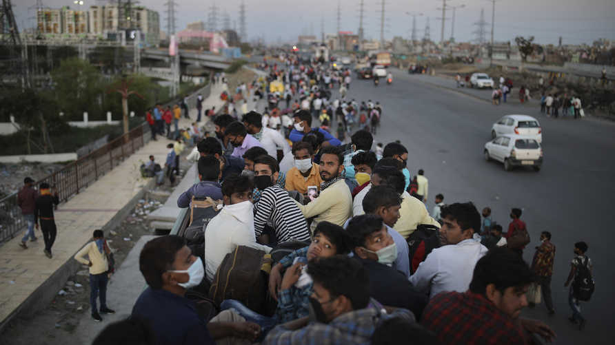 Indian migrant workers sit atop a bus, provided by the government, as others walk along an expressway to their villages…